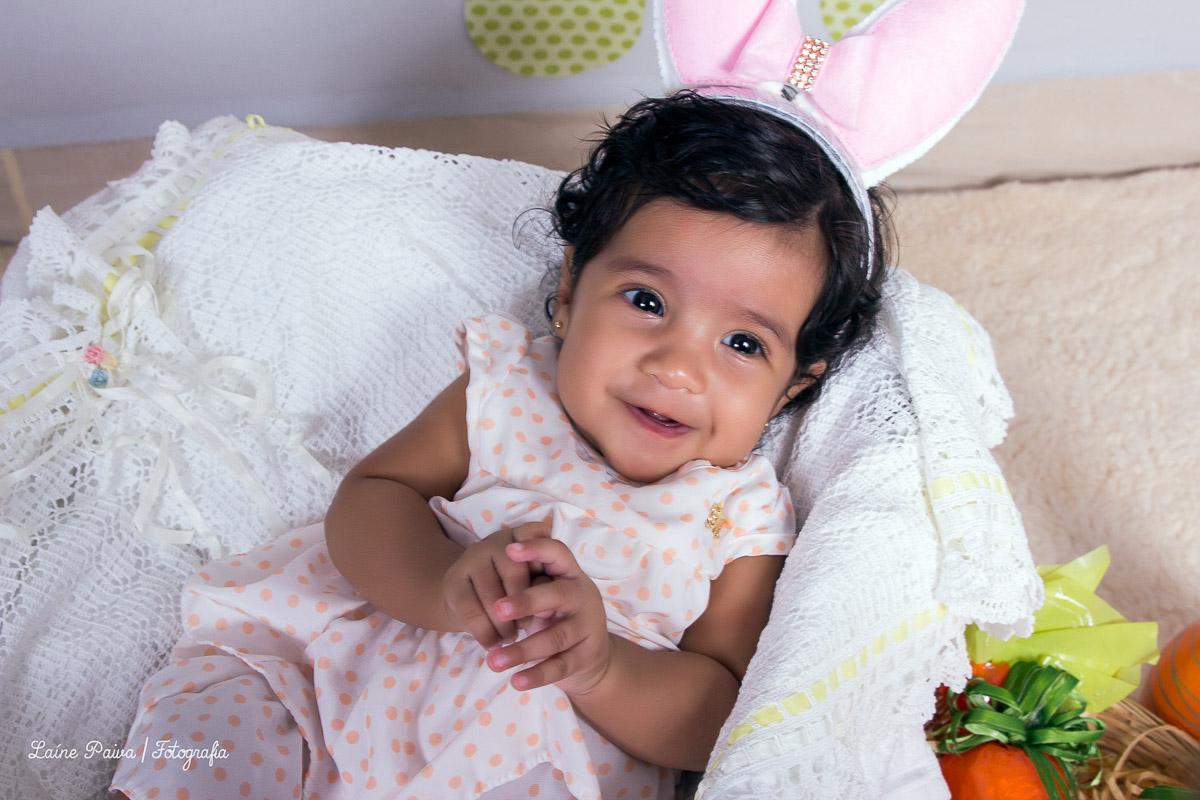 Bebe de 3 meses, menina, acompanhamento infantil com o tema de pascoa, deitada dentro de um caixote de madeira com tecido dentro. Cenario com bandeirolas de coelhos, pegadas no châo, cesto com ovos feito de gesso, tudo para compor o cenario de pasco