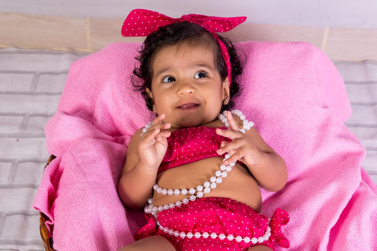 acompanhamento infantil de um menina com 4 meses. Criança dentro de cesto com tecido rosa. Conjunto de roupinha composto por saia, top e tiara rosa com bolinhas brancas. Perolas brancas colocadas no pescoço da criança.