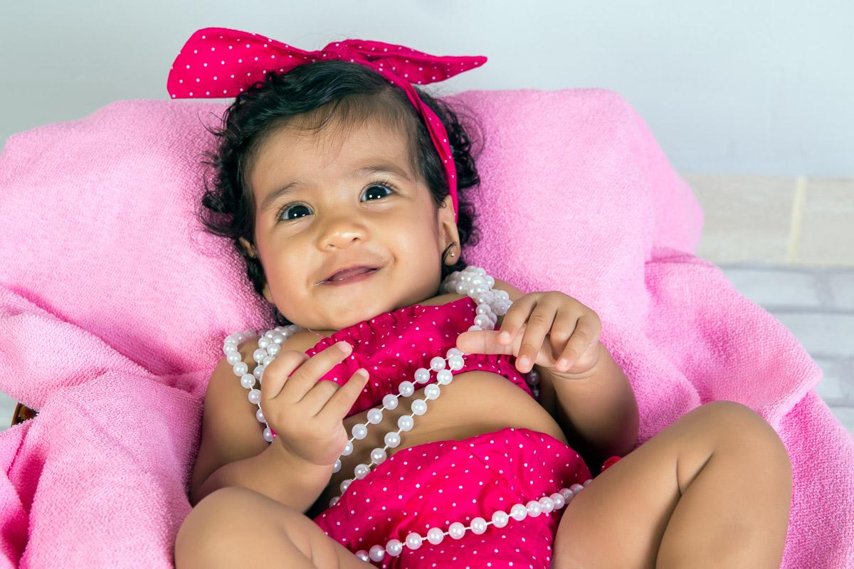 acompanhamento infantil de um menina com 4 meses. Criança dentro de cesto com tecido rosa. Conjunto de roupinha composto por saia, top e tiara rosa com bolinhas brancas. Perolas brancas colocadas no pescoço da criança. Cenario com pis