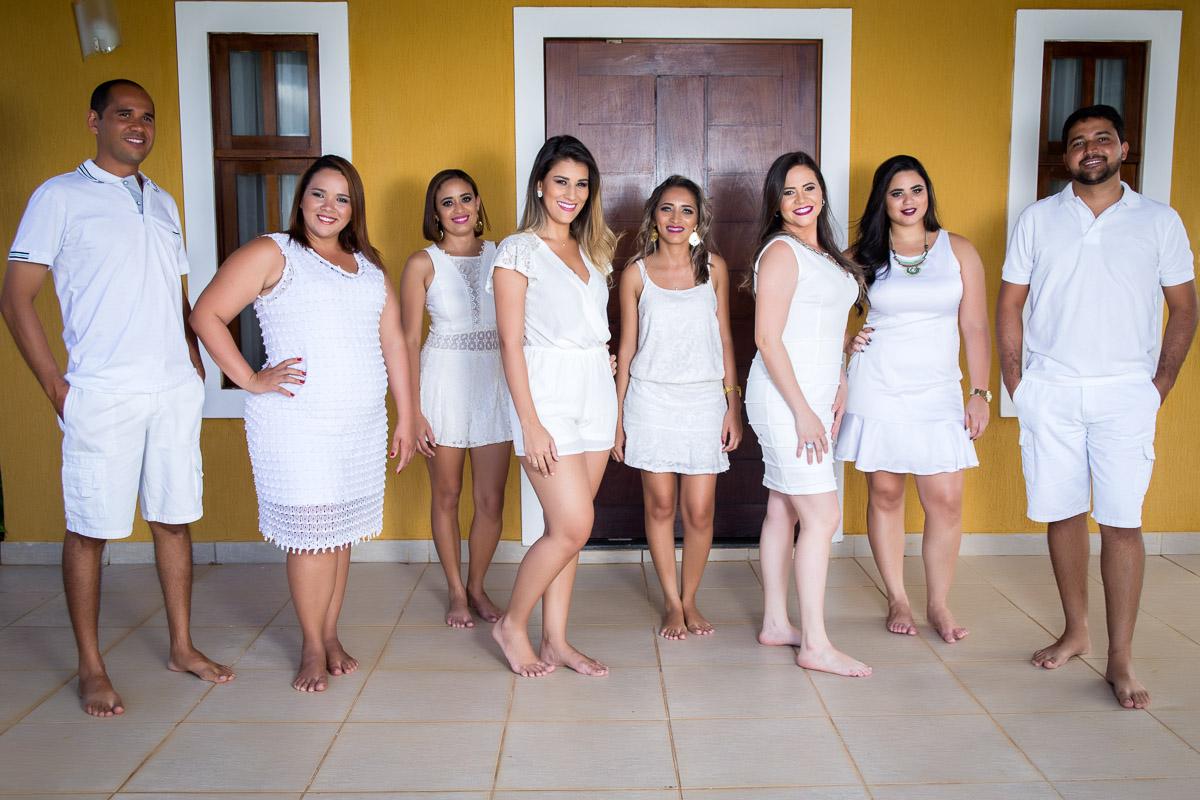 formandos vestidos de branco em frente a parede amarela com porta de madeira