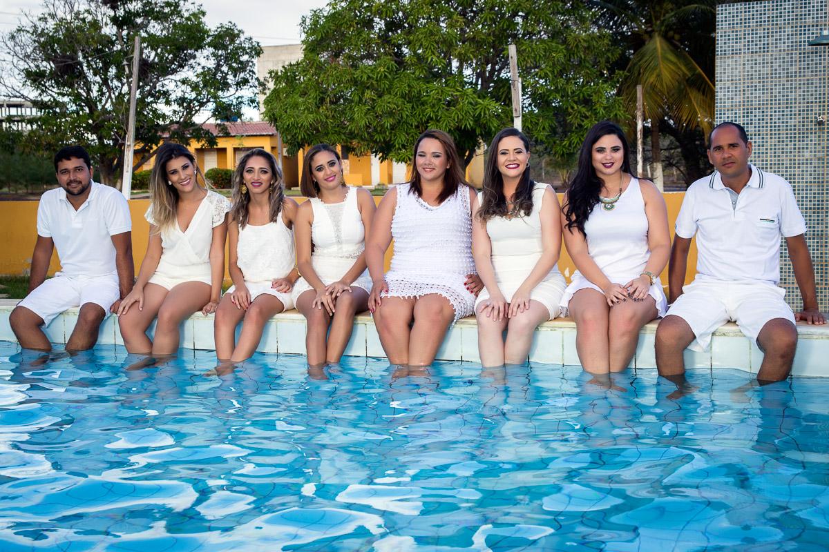 formandos vestidos de branco com pés dentro de piscina