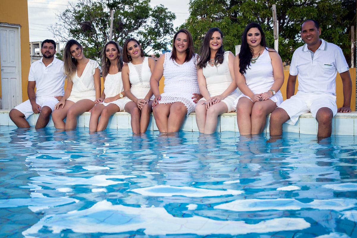 formados sentados vestidos de branco com pés dentro de piscina