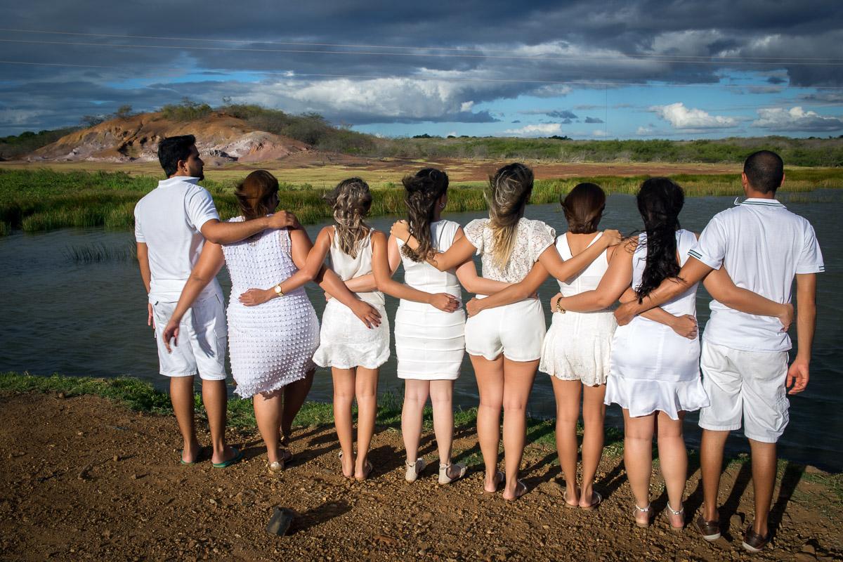 formandos abraçados vestidos de branco em frente ao rio