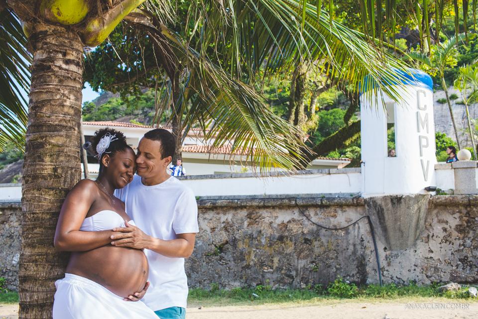 Casal grávido recostado em um coqueiro, iluminado por raios de sol que passa por entre as folhas daa árvores. Ele segura a barriga dela