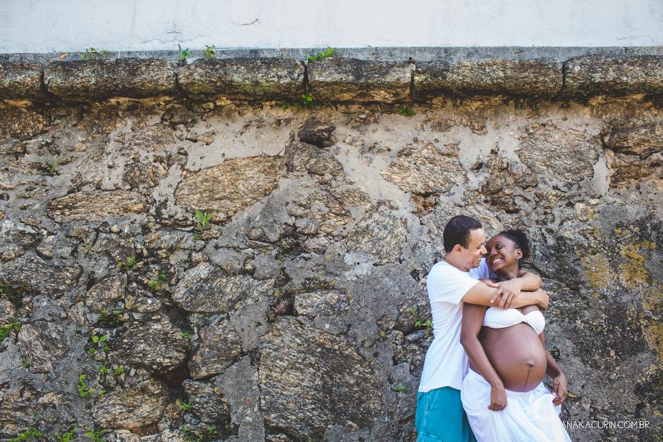 Casal grávido abraçado com parede de pedra ao fundo. Ela o olha ternamente