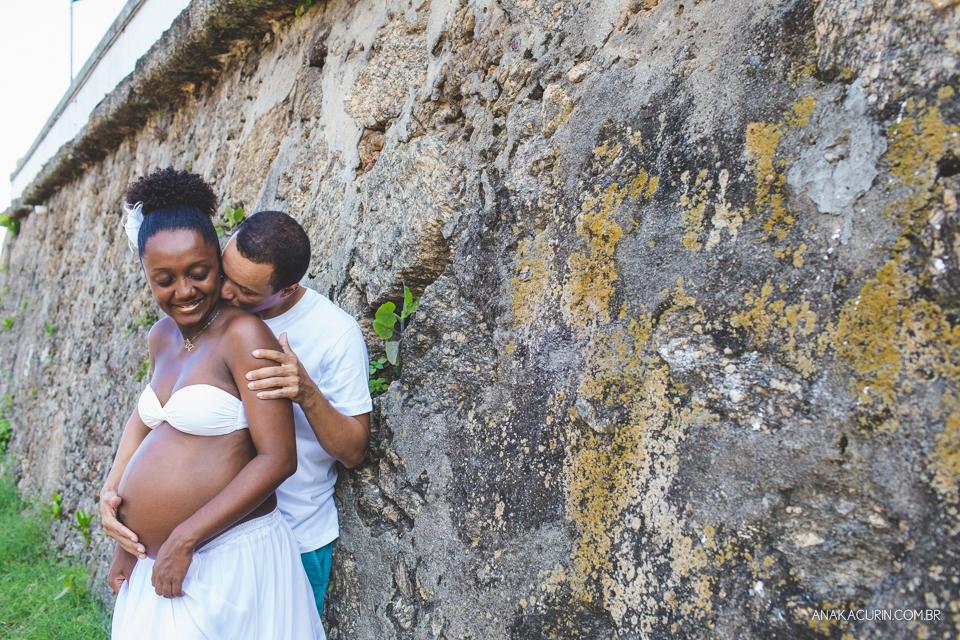 Casal grávido abraçado com parede de pedra ao fundo. Ele beija o pescoço dela com carinho