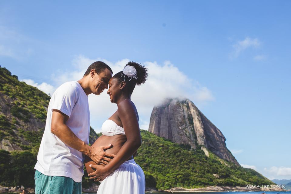Casal grávido se olhando com o Pão de Açúcar ao fundo, no Rio de Janeiro