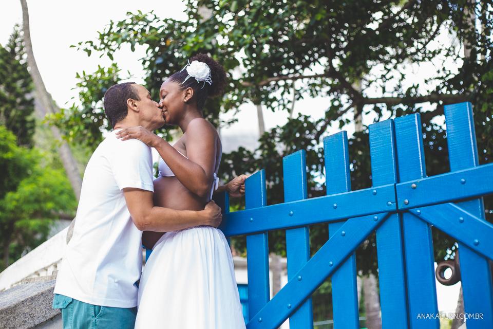 Casal grávido se entreolhando e sorrindo ao topo de uma escadaria com um portão azul ao fundo