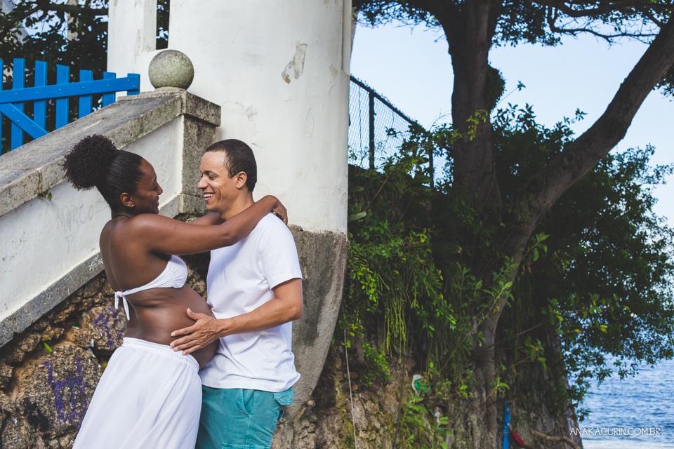Casal grávido se abraça aos pés da escada com a praia ao fundo