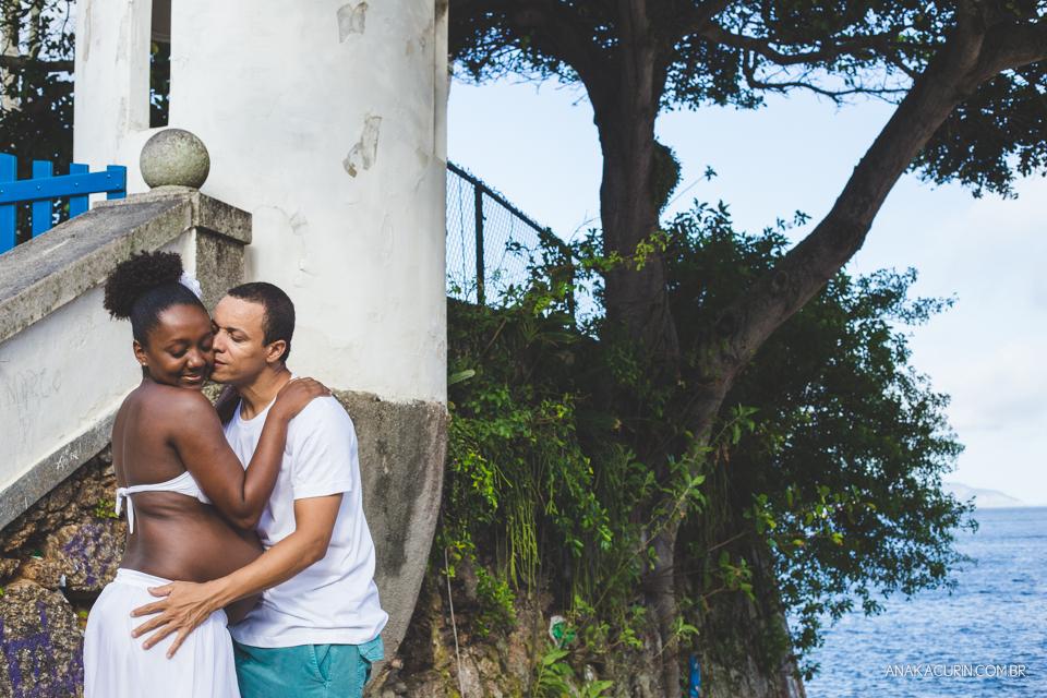 Casal grávido se abraça aos pés da escada com a praia ao fundo, ele a beija no rosto