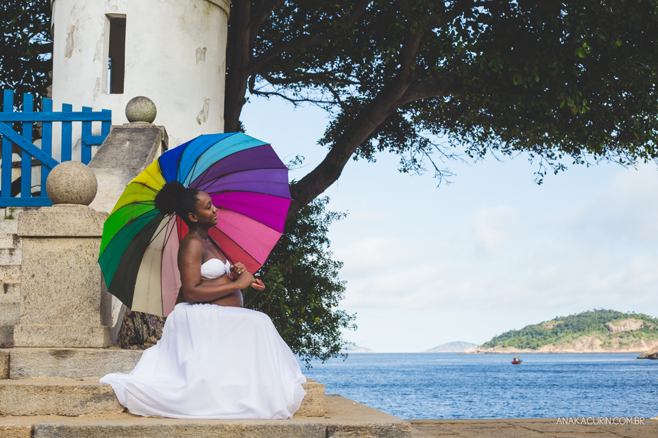 Grávida vestida de branco sentada em uma escada com praia ao fundo, segura uma sombrinha com as cores do arco-íris