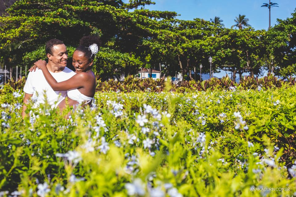 Casal se abraça em meio a uma plantação de flores ensolarada. Céu azul ao fundo