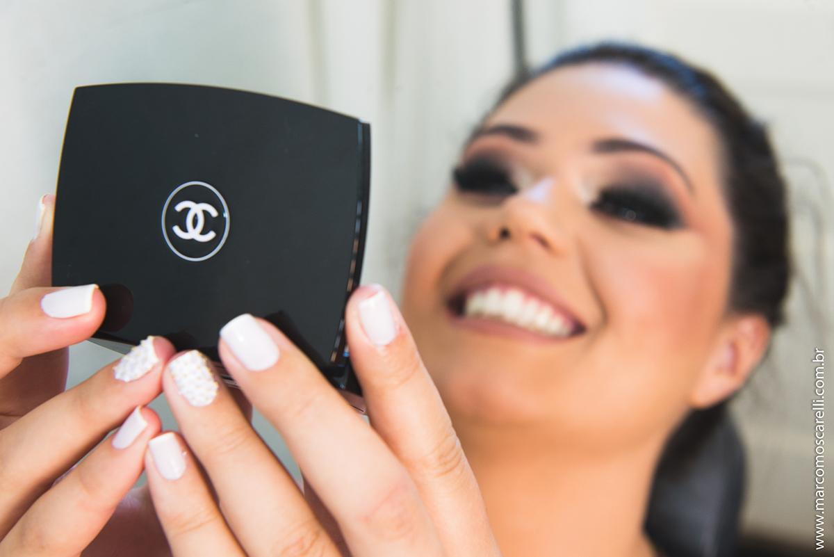 formanda conferindo a maquiagem em espelho de mão