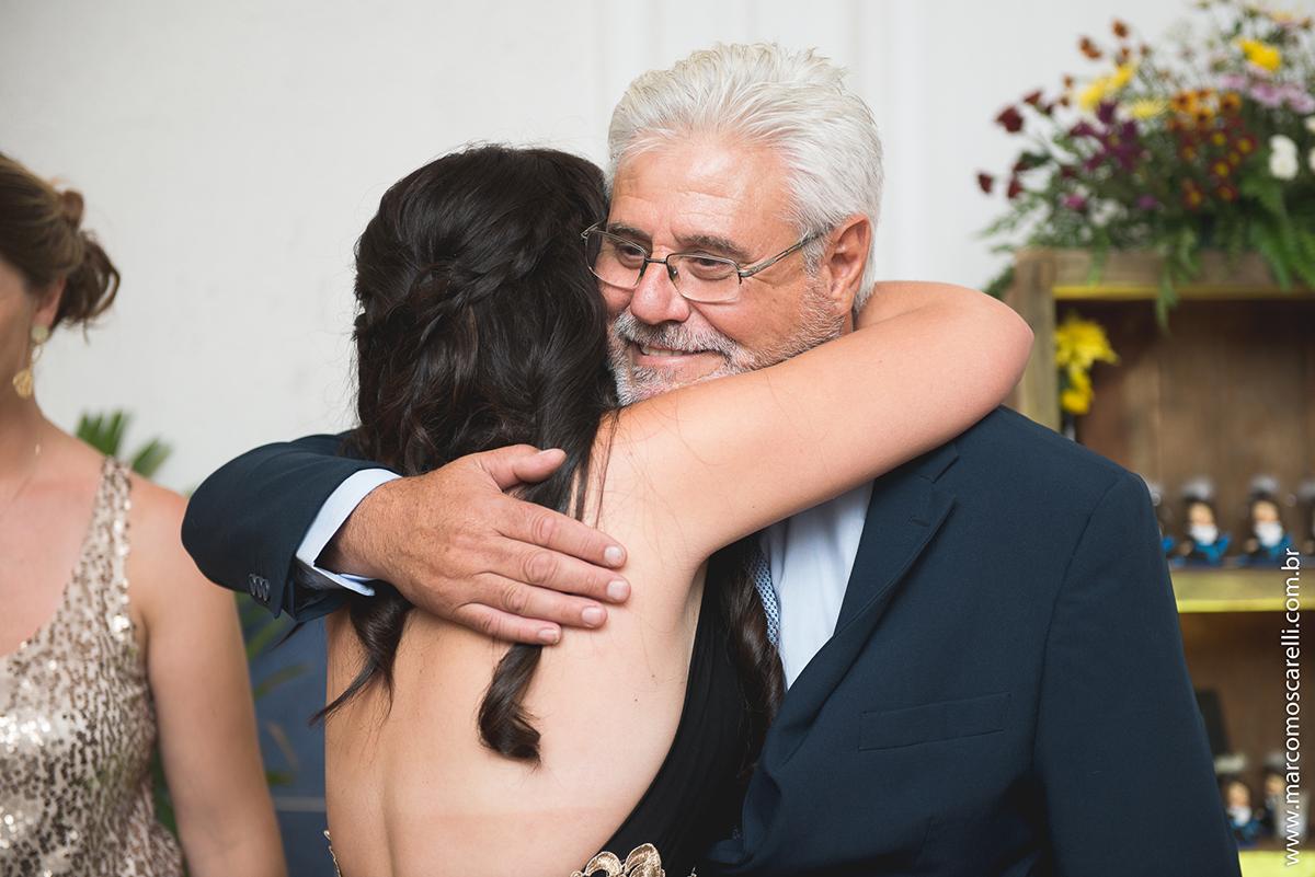 Fromanda abraçando seu pai na recepção de formatura de Marketing