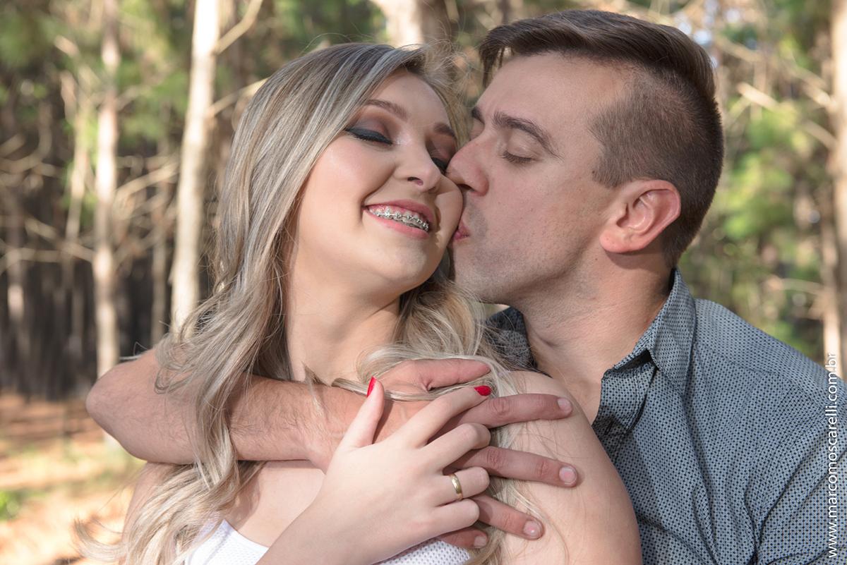 Noivo beijando rosto da noiva durante ensaio realizado no las acacias em Pelotas antes do dia do casamento. Ensaio pré wedding. Foto por Marco Moscarelli Fotografo .