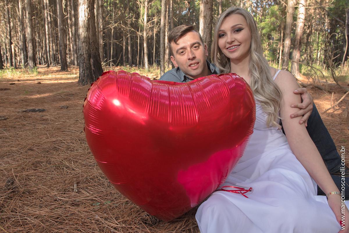 Casal de noivos posando para foto com balão em forma de coração durante ensaio pré wedding no las acacias em Pelotas.Foto por Marco Moscarelli Fotografo