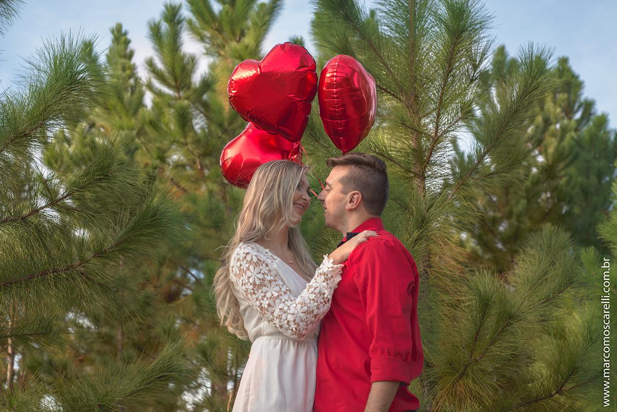 Casal de noivos em momento lindo com baloes vermelhos em forma de coração durante ensaio pré casamento. Pré wedding realizado no Las Acacias em Pelotas. Foto por Marco Moscarelli Fotografo