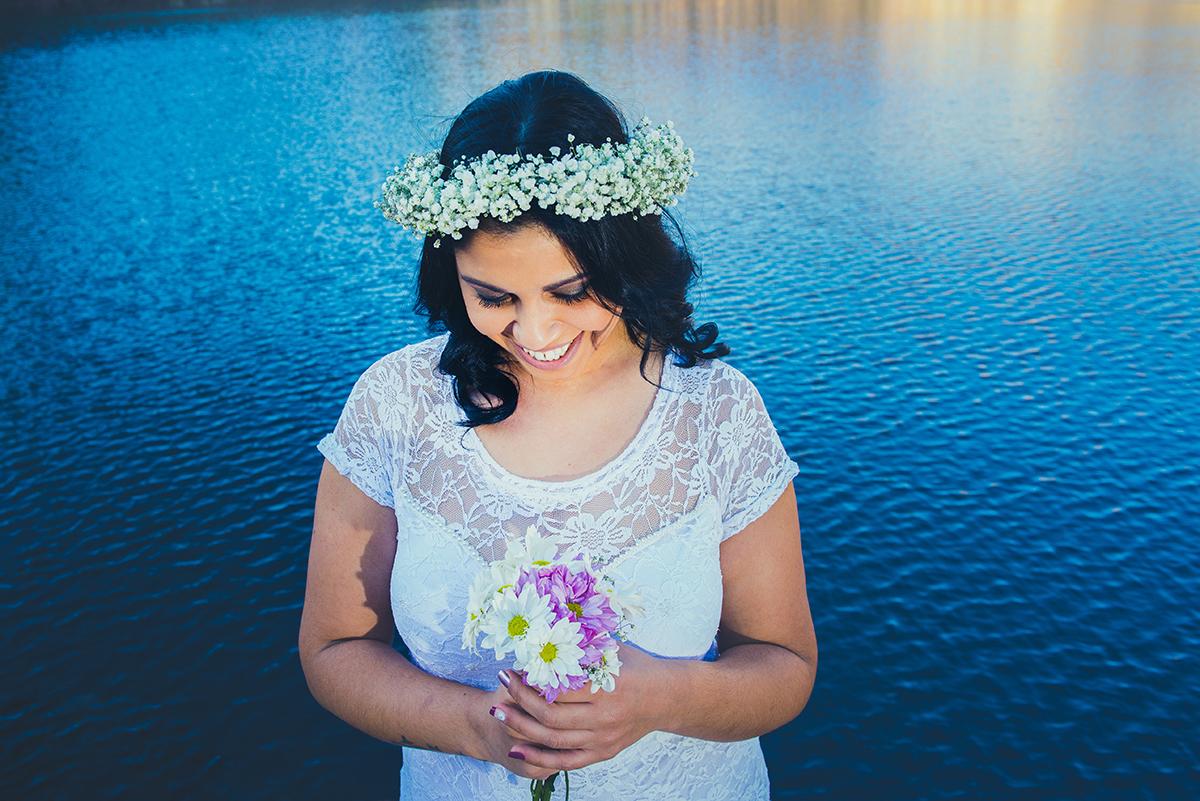 Noiva dando lindo sorriso para o seu buque de noiva com o lazo azul das Minas do camaquã ao fundo em seu ensaio pré wedding