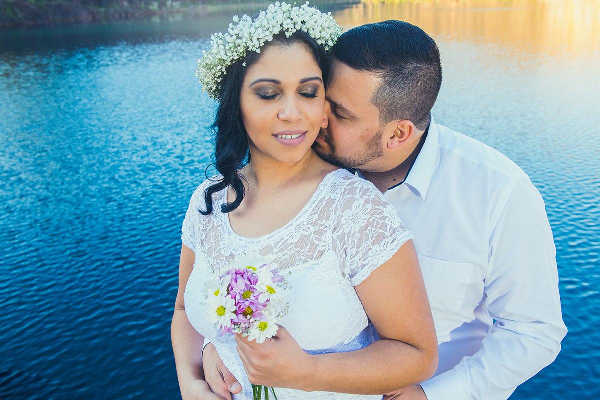 Noivo beijando pescoço da noiva abraçando por tras com lindo lago azul das Minas do Camaquã ao fundo em enasaio pré wedding.