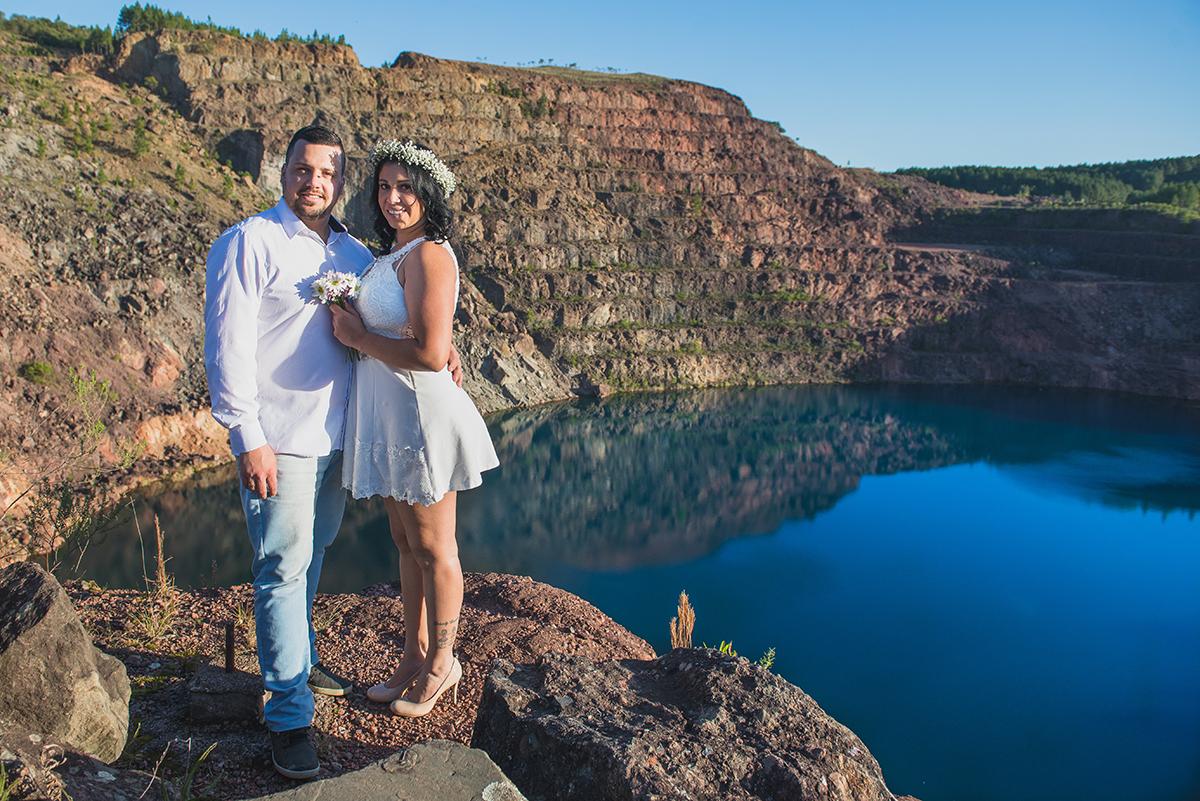 Noivos posando para foto com o lago azul das minas do camaquã ao fundo durante ensaio de casalmento pré wedding.