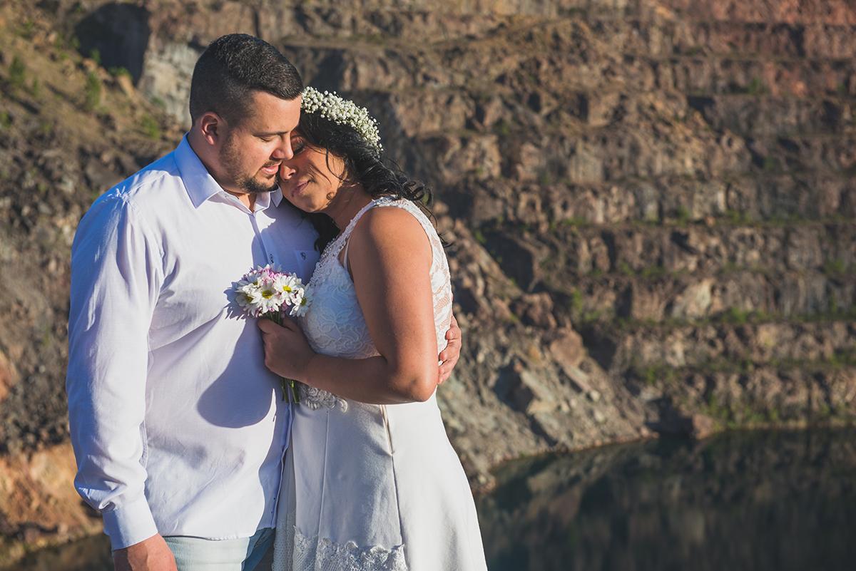 Noivos posando para foto com o lago azul das minas do camaquã ao fundo durante ensaio de casalmento pré wedding