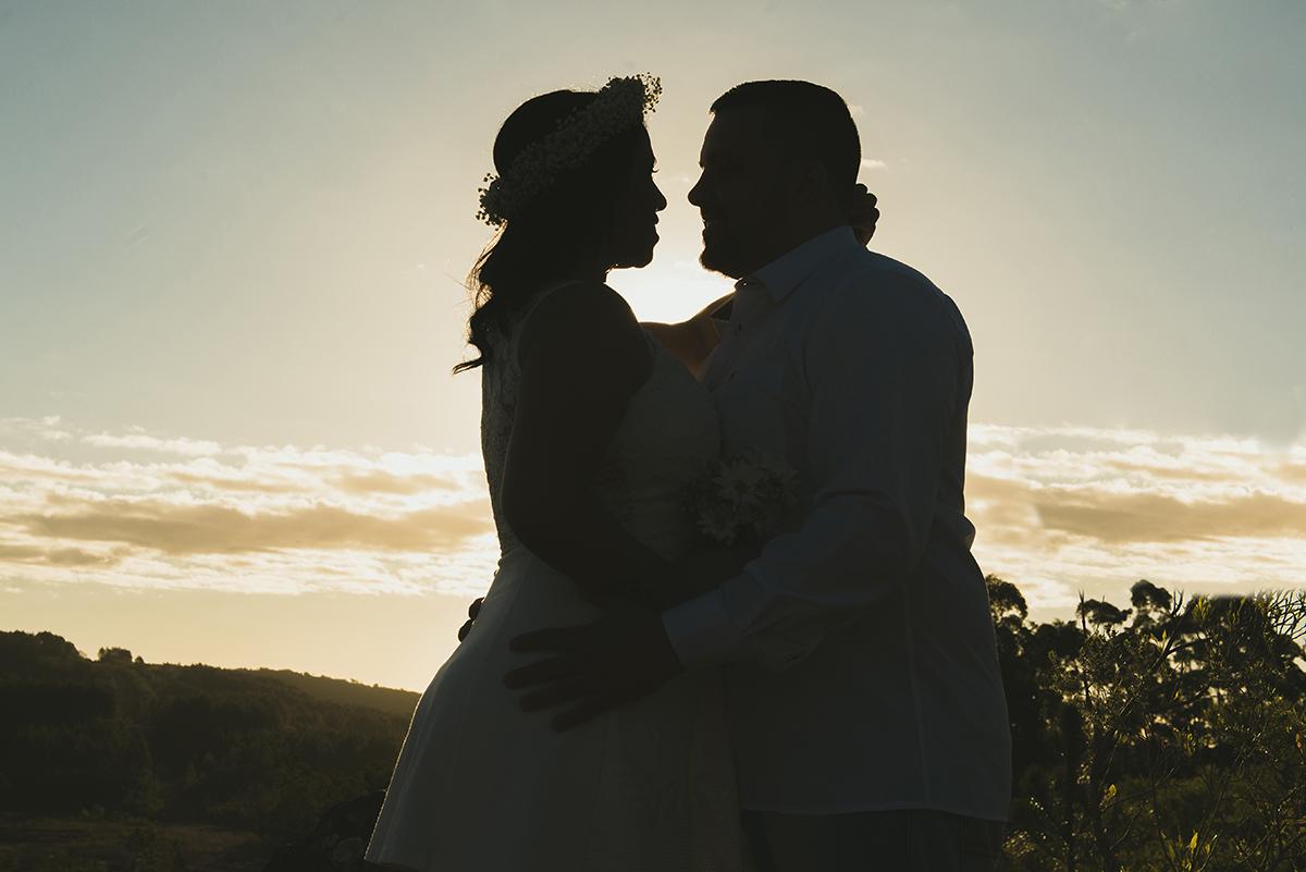 Linda foto contra a luz do casal de noivos em seu ensaio pré wedding realizado antes do casamento nas minas do camaquã