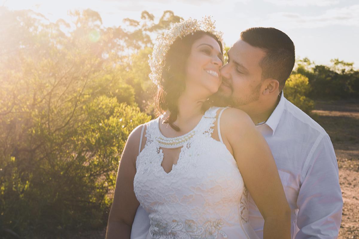 Linda foto contra a luz com a luz do sol entrando com tons amarelados do casal de noivos em seu ensaio pré wedding realizado antes do casamento nas minas do camaquã