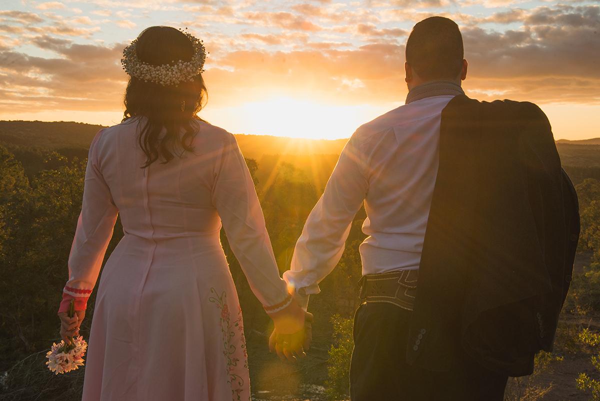 Noivo de mãos dadas com a noiva admirando o por do sol durante ensaio pré wedding antes do casamento nas minas do camaquã.