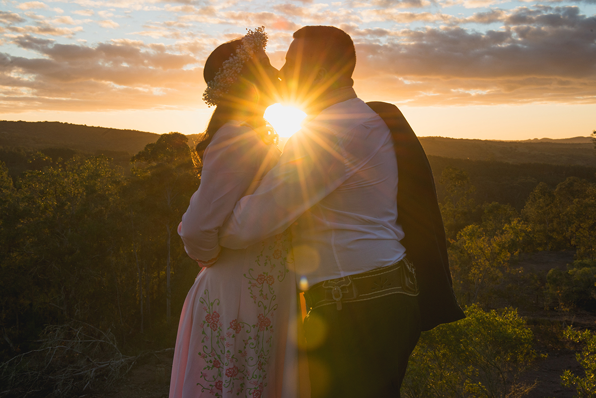 Foto do beijo dos noivos quase conra a luz do sol durante ensaio de casal.