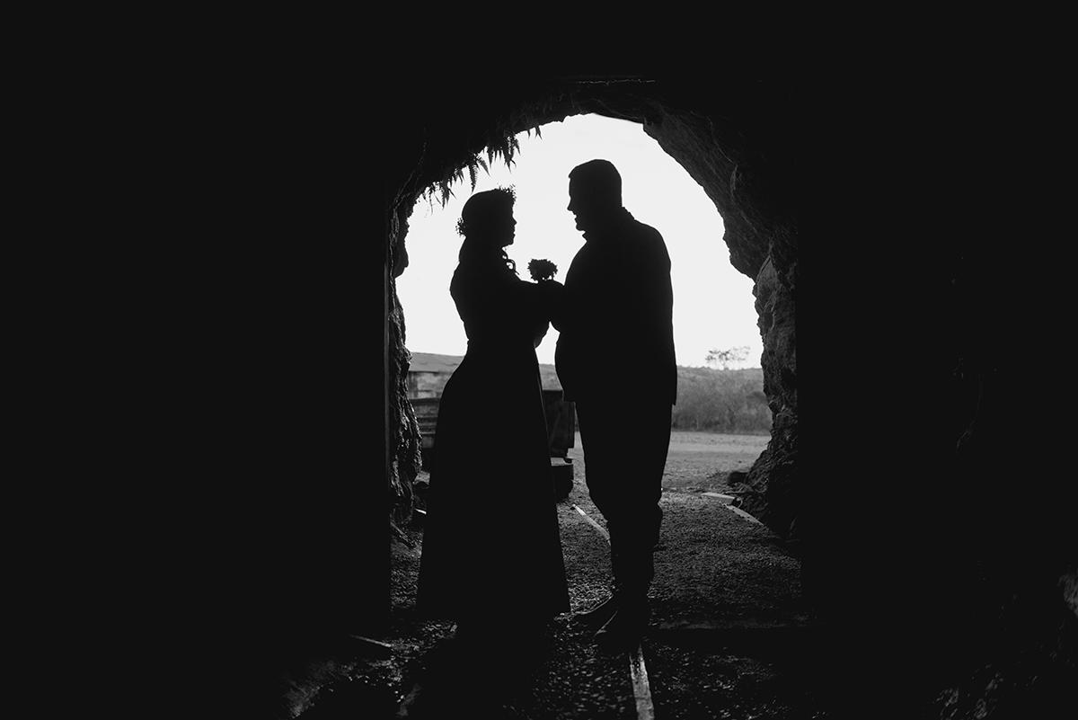 Foto contra a luz em preto e branco do casal de noivos na entrada de um tunel ferroviário nas minas do camaquã durante ensaio do casal em seu pré wedding.