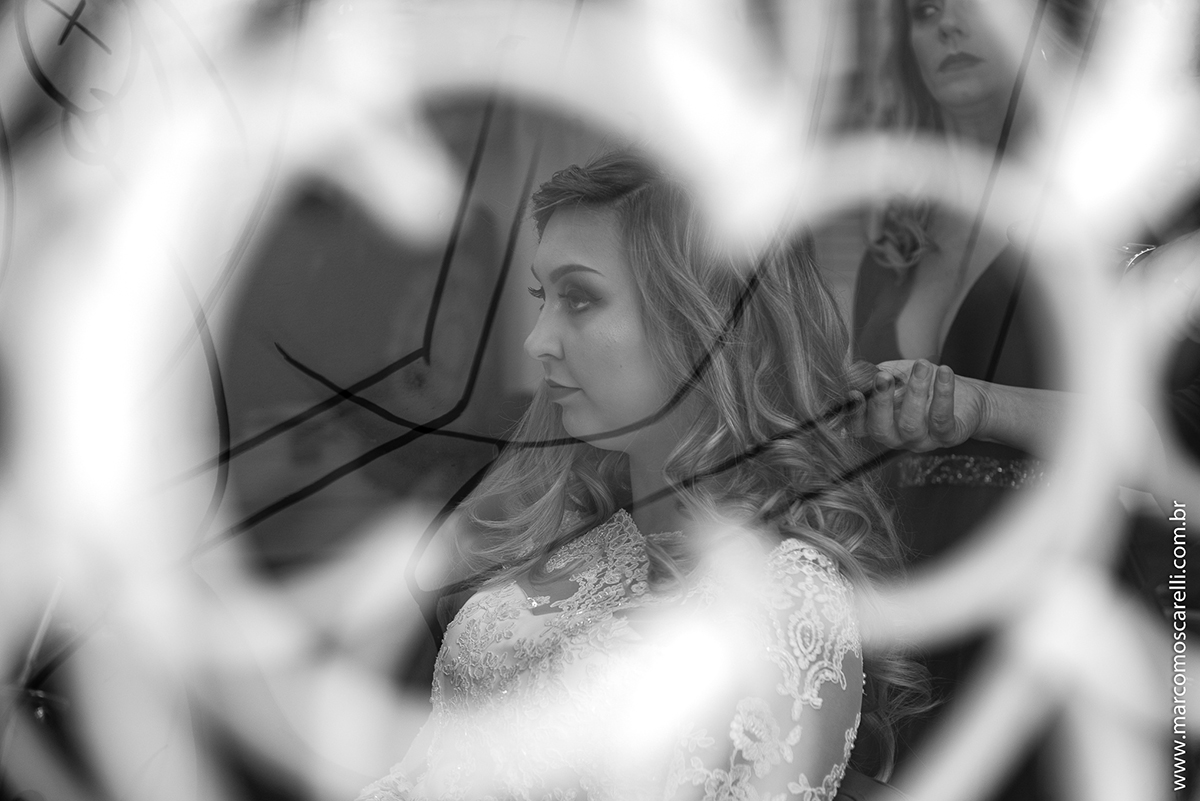Foto em Preto e Branco da noiva atravas do vidro em quanto faz a maquiagem no Making of da noiva. Foto-Marco Moscarelli