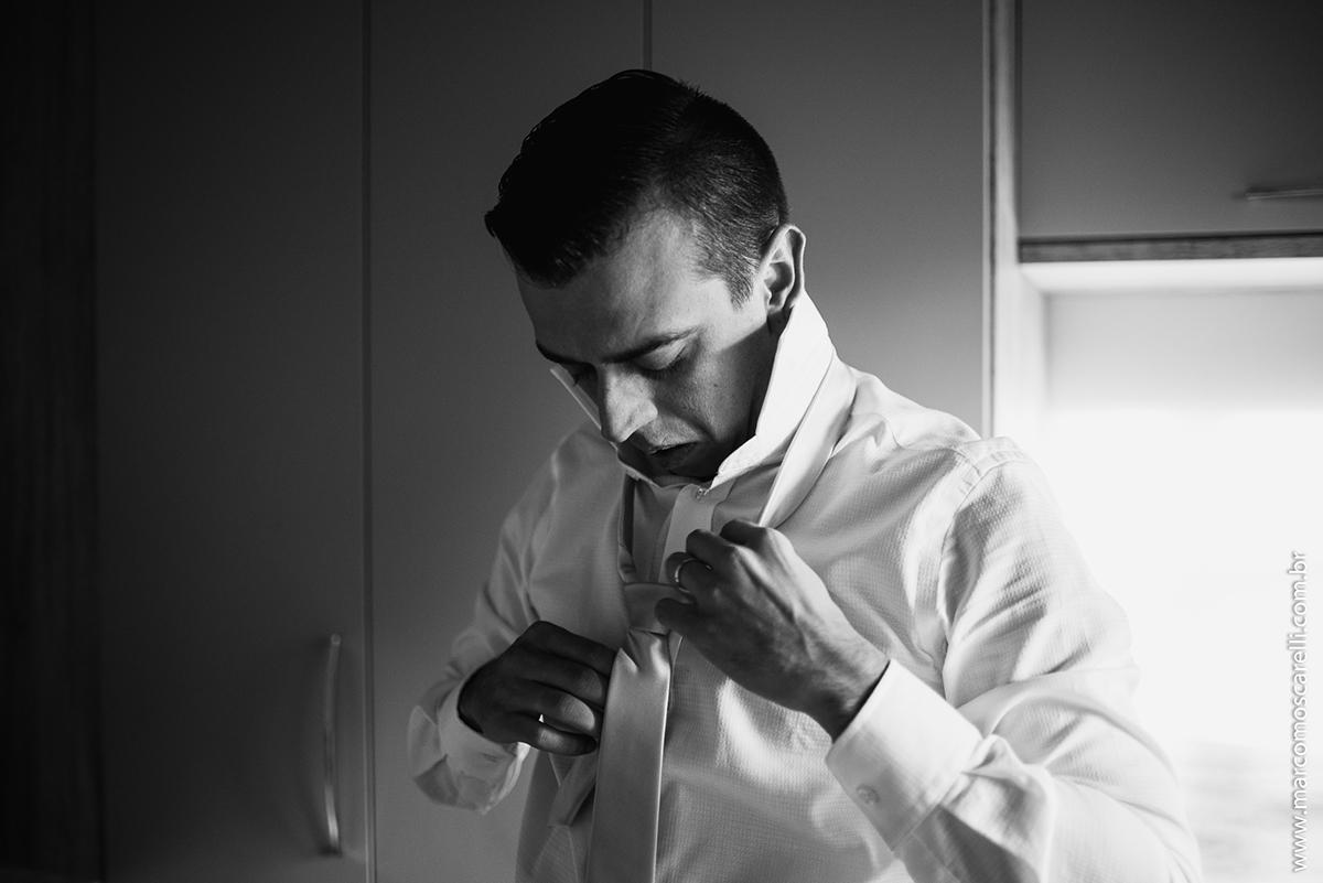 Foto em preto e branco do noivo arrumando a gravata durante Making of antes do casamento. Foto- Marco Moscarelli