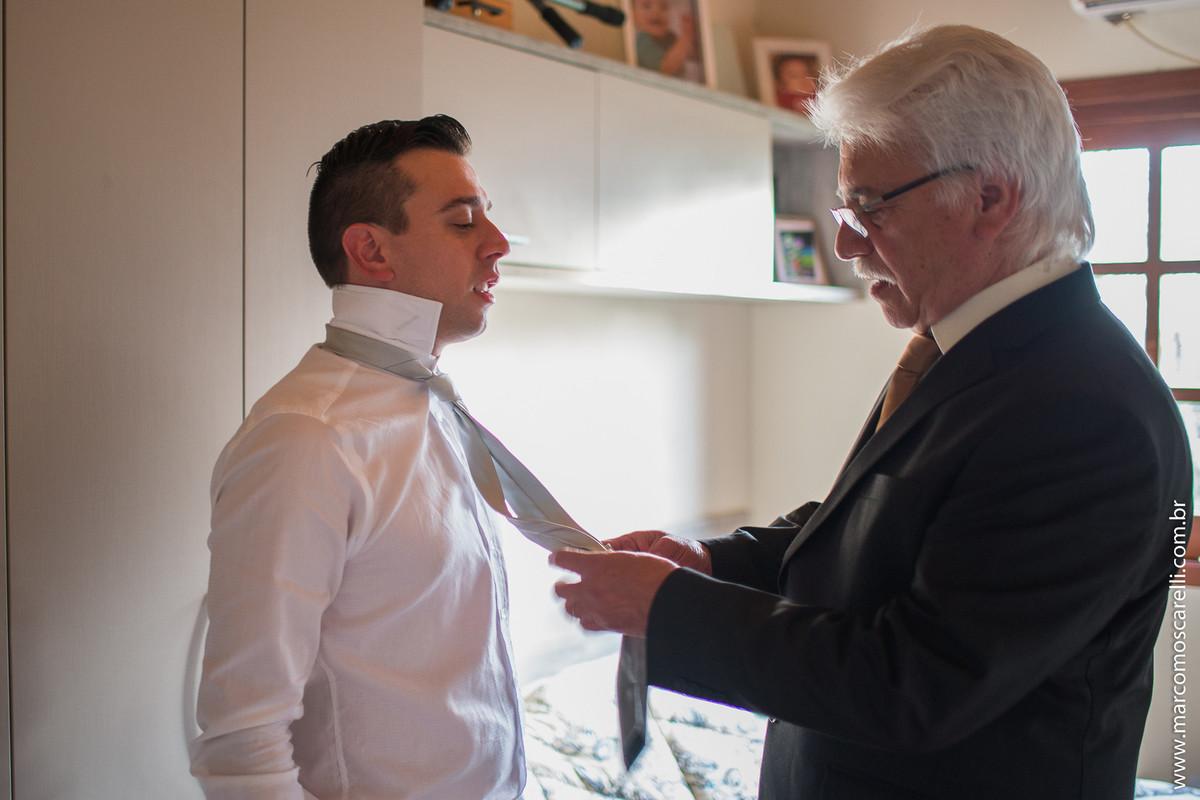 Foto do momento em qu eo pai do noivo ajuda com o nó da gravata durante Making of do noivo antes do casamento. Foto por Marco Moscarelli