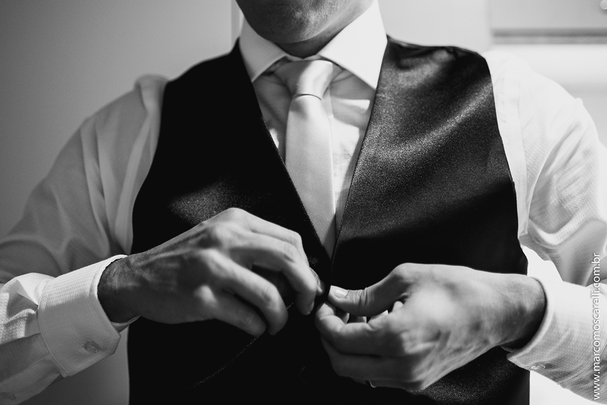 Foto do detalhe do noivo abotoando o colete durante Making of antes do casamento. Foto por Marco Moscarelli