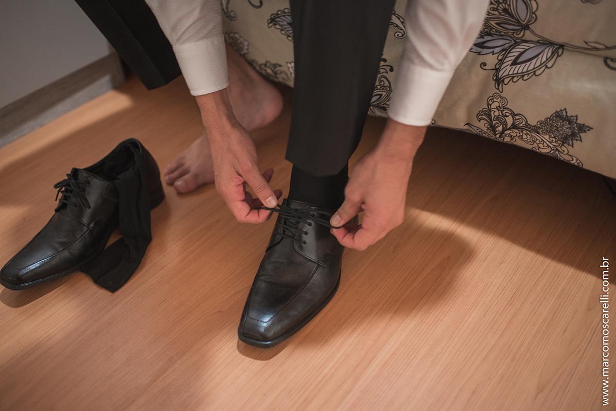 Foto do detalhe do noivo amarrando o cadarço do sapato durante o Making of antes do casamento. Foto por Marco Moscarelli