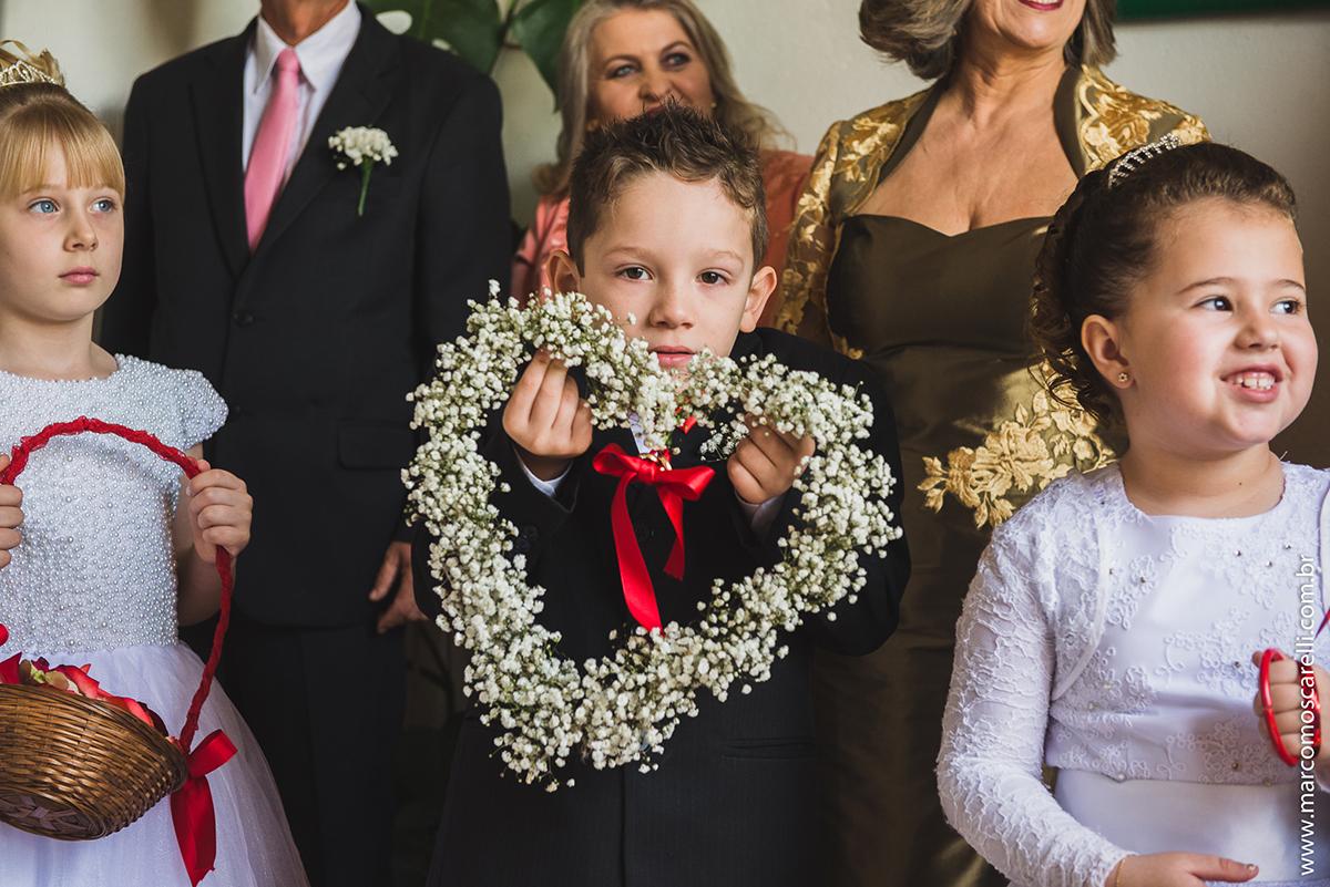 Retrato do pagem do casamento segurando um coração de flores enquanto aguarda a noiva chegar para o casamento. Foto por Marco Moscarelli