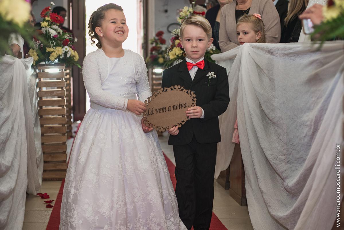 Entrada do pagem e da aia segurando plaquinha de maderia que diz lá vem a noiva durante o casamento. Foto por Marco Moscarelli