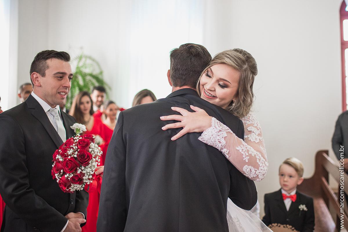 Foto da noiva abraçando o noivo na cerimônia de casamento. Foto por Marco Moscarelli