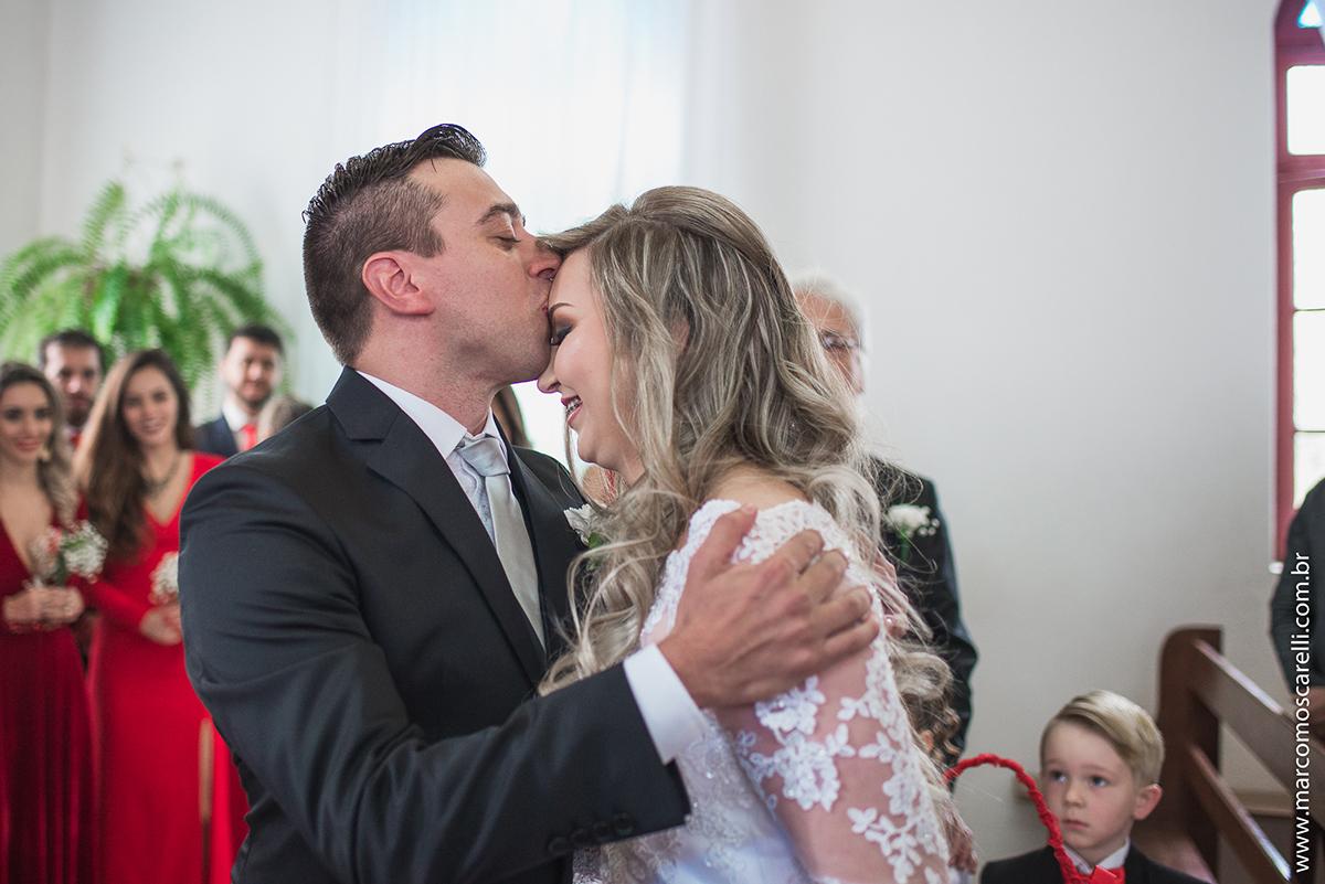 Noivo beijando a testa da noiva durante o casamento. Foto por Marco Moscarelli