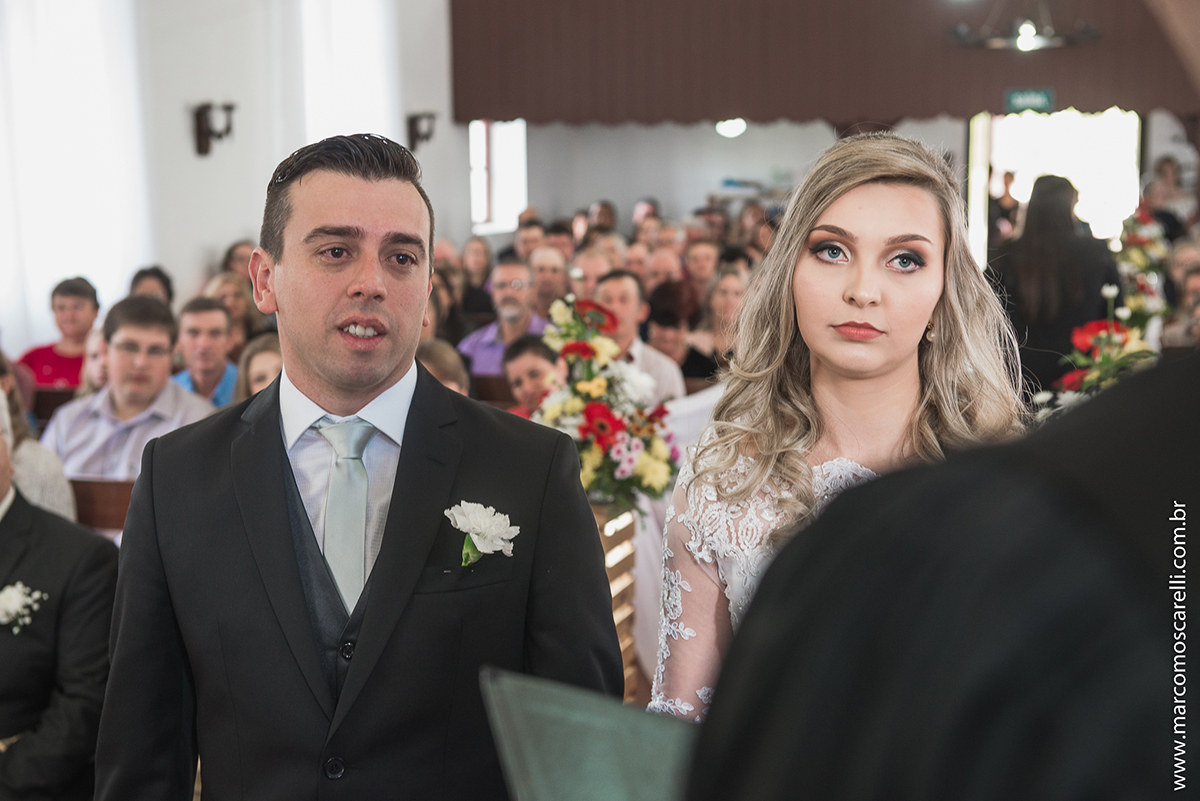 Foto do casal de noivos no altar com a nave da igreja de fundo. Foto por Marco Moscarelli