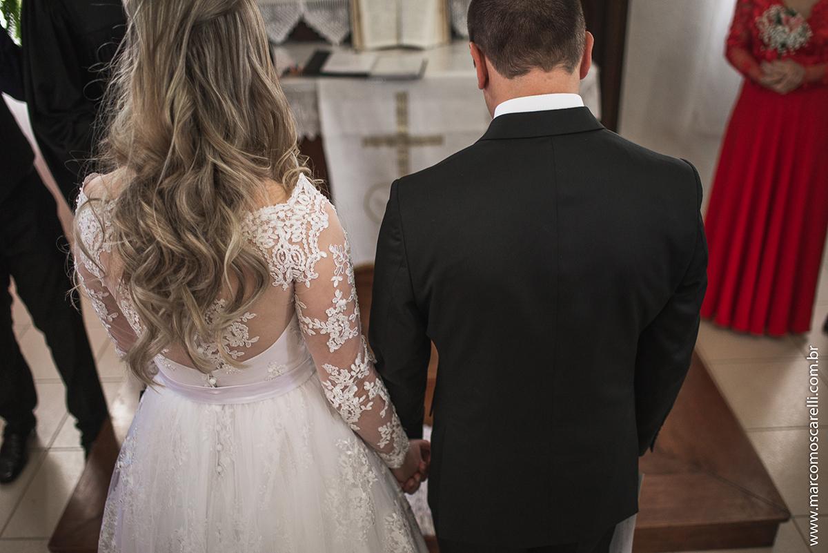 Foto dos noivos ajoelhados no altar durtante o casamento. Foto por Marco Moscarelli