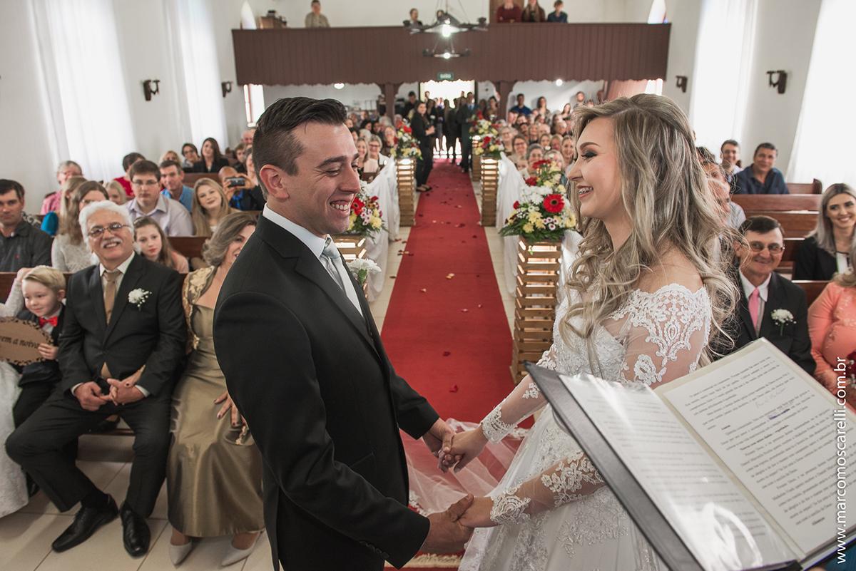 Noivos de mãos dadas no altar da igreja durante o casamento. Foto por Marco Moscarelli