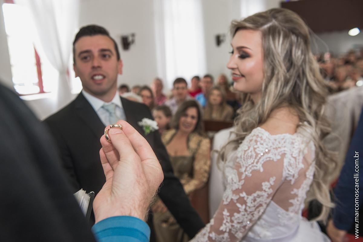 Fotografia das alinças de casamento na mão do pastor com os noivos desfocados ao fundo. Foto por Marco Moscarelli