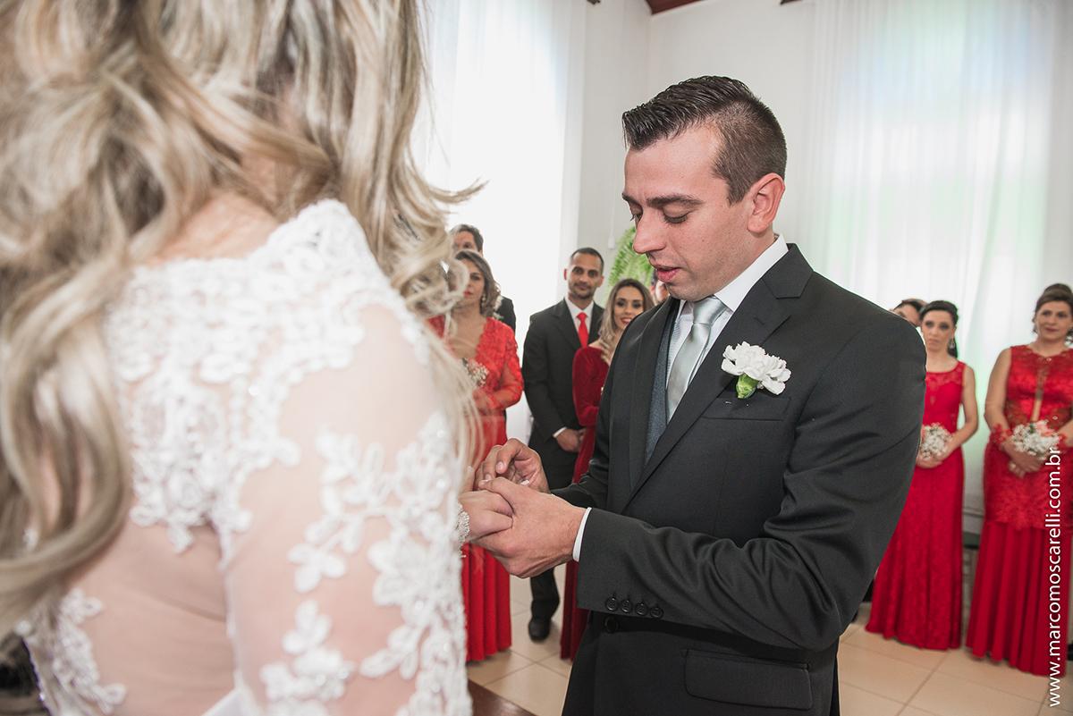 Noivo colocando a alinça no dedo da noiva durante o casamento. Foto por Marco Moscarelli