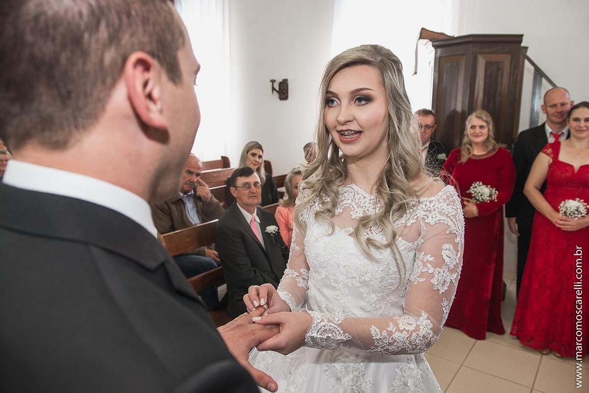Noiva colocando a aliança no dedo do noivo durante o casamento. Foto por Marco Moscarelli