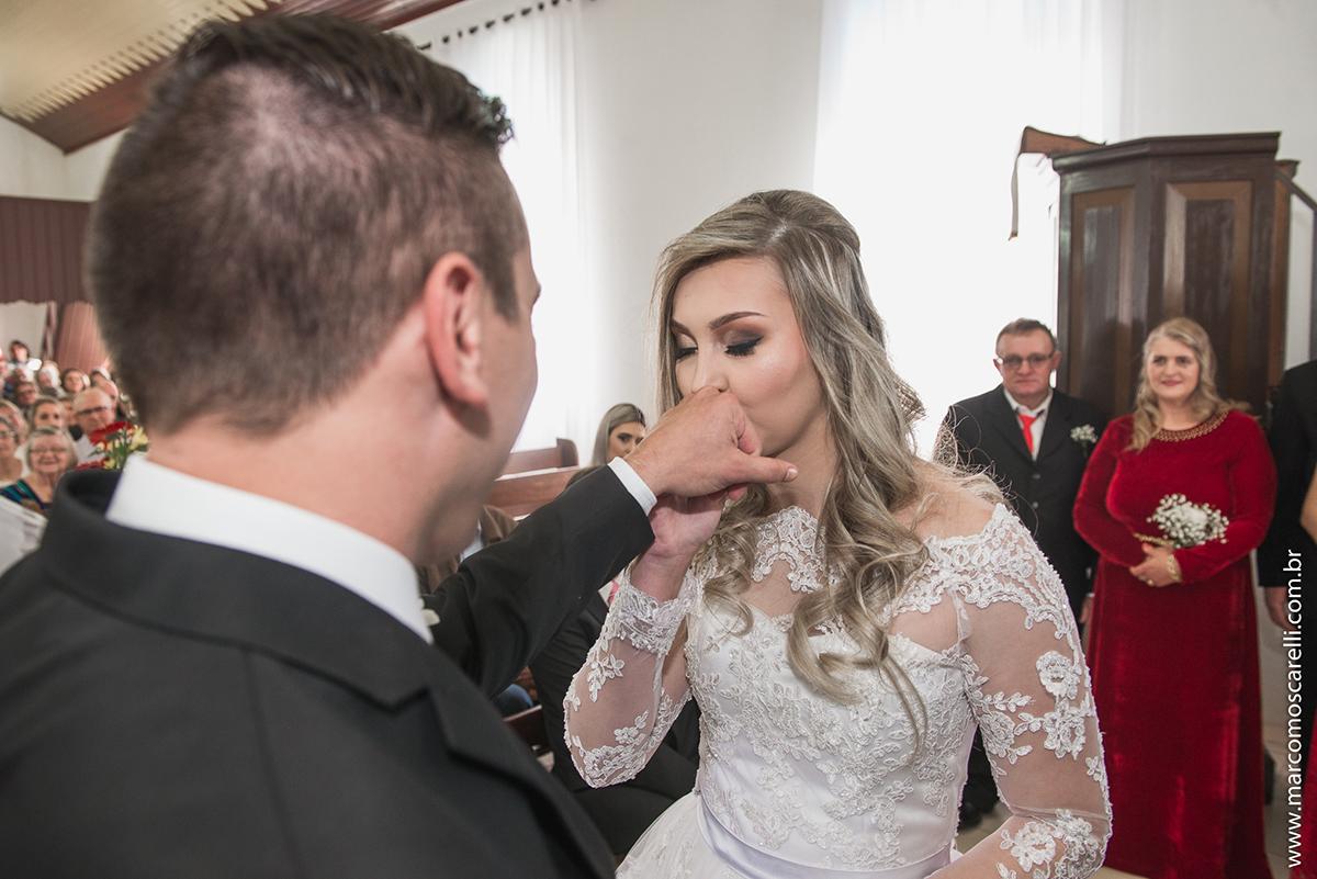 Noiva beijando a mão do noivo logo após colocar a alinaça durante o casamento. Foto por Marco Moscarelli