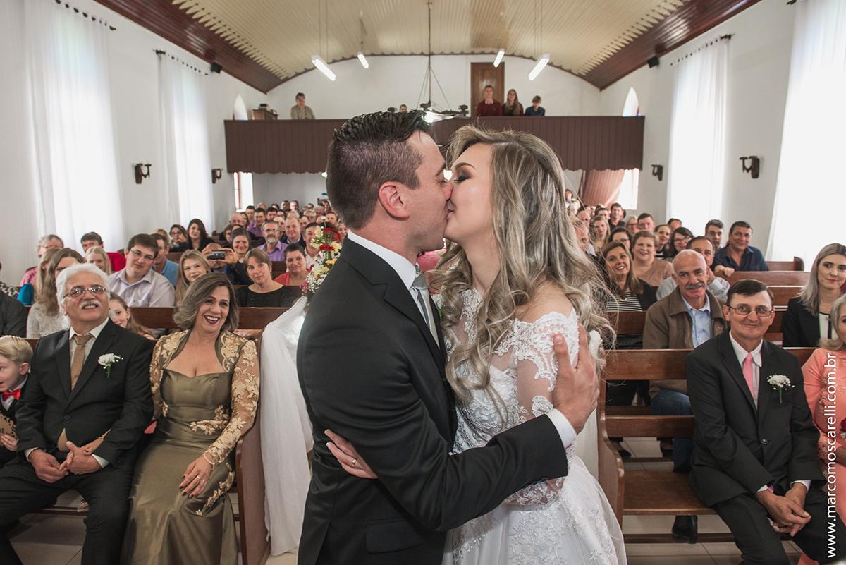 Beijo dos noivos ao final do casamento com a nave da igreja ao fundo. Foto por Marco Moscarelli
