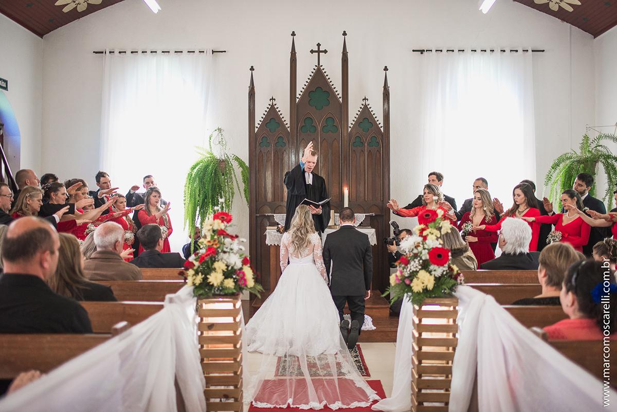 Noivos ajoelhados no altar durtante o casamento. Foto por Marco Moscarelli