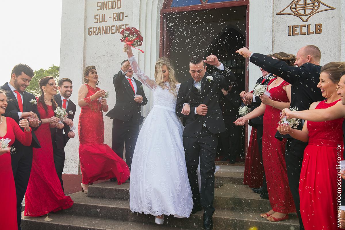 Saida dos noivos da igreja, Noiva levantando o buque para cima com um lindo sorriso. Foto por Marco Moscarelli