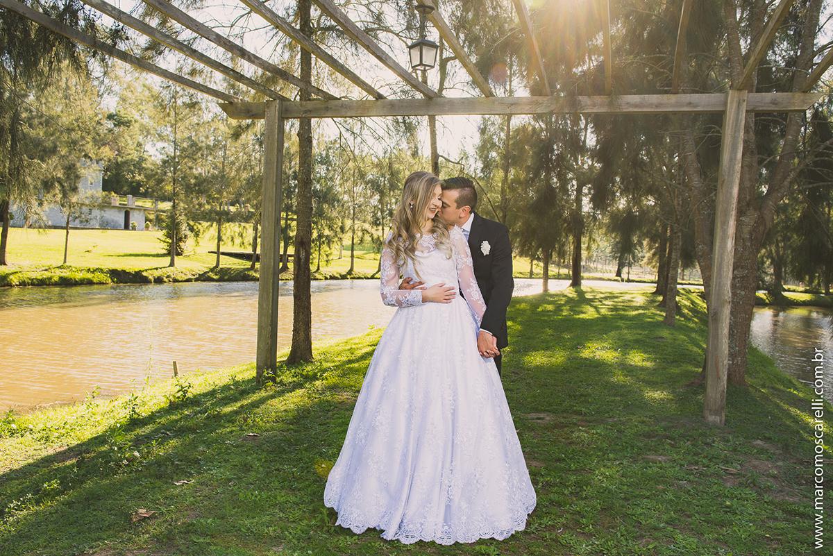 Ensaio dos noivos pós casamento, foto dos noivos ewmldurados por pegolado de maderia com o sol iluminando o vestido da noiva e formando uma bela imagem. Foto por Marco Moscarelli